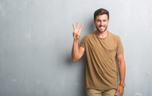 Handsome Young Man Over Grey Grunge Wall Showing And Pointing Up With Fingers Number Three While Smiling Confident And Happy.