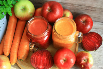 Apple, carrot and beet juices, fruits and vegetables in the background