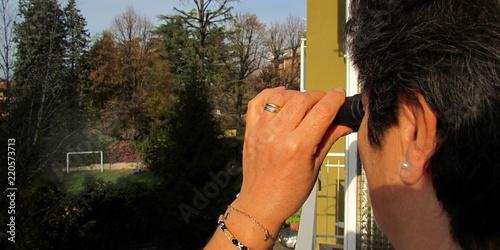 Fotografía  Donna curiosa con il binocolo