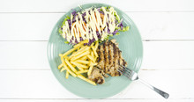 Pork Steak In A Blue Dish On A White Wood Floor Table And French Fries, Green Salad, Purple Cauliflower,Top View. .