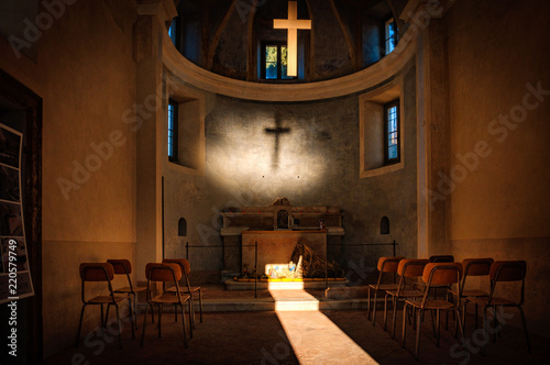 A cross projecting a shadow in a small rural church set up with a nativity scene Canvas Print