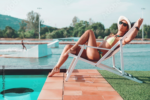 Obraz na plátne Young slim woman in bikini, straw hat and sunglasses relax near swimming pool in