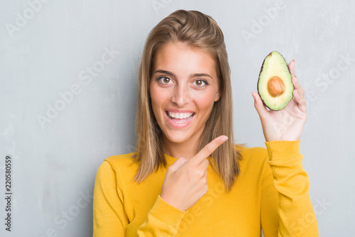 Slika na platnu Beautiful young woman over grunge grey wall eating avocado very happy pointing w