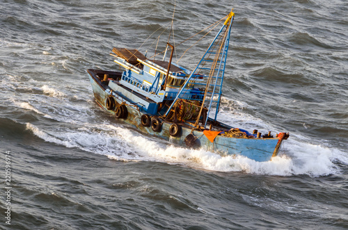Tuinposter Zeilen Fishing boat in a stormy sea