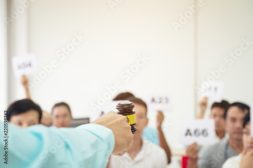 Photo Close up auctioneer hand, holding gavel, wooden hammer, and blur group of people in auction room, one man raising hand up for bidding