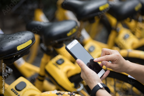 Valokuva  People hands using smartphone scanning the QR code of shared bike in city