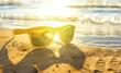 stylish yellow sunglasses by sea, yellow sand, sun, depth of field, blur