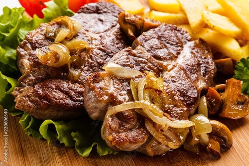 Grilled steak with french fries and vegetables on white background
