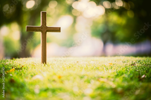 The cross standing on meadow sunset and bokeh background Wallpaper Mural