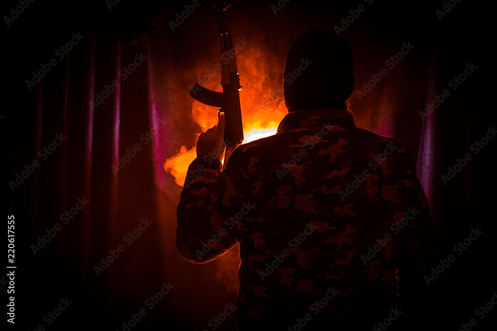 Fototapeta Silhouette of man with assault rifle ready to attack on dark toned foggy background or dangerous bandit in black wearing balaclava and holding gun in hand.