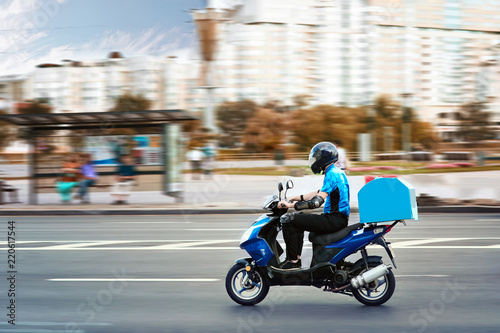 Fototapeta premium Chłopak na wynos na hulajnodze ze skrzynką bagażnika jeżdżącą w pośpiechu. Kurier dostarczający żywność przez skuter, aby uniknąć korków.