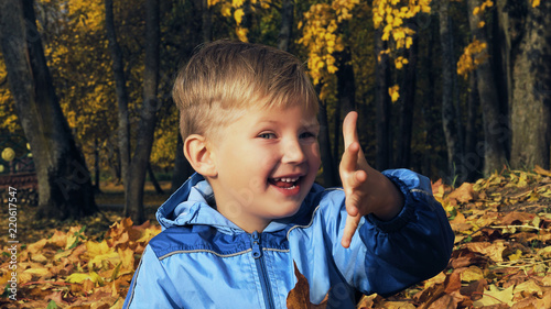 Valokuvatapetti Little Caucasian smiling boy sitting with bouquet of yellow leaves on the ground