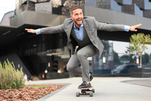 Confident Young Businessman In Business Suit On Longboard Hurrying To His Office, On The Street In The City