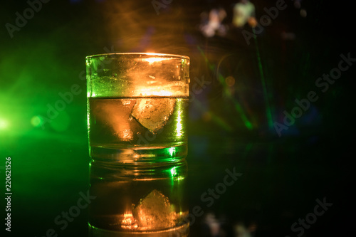 Deurstickers Alcohol selective focus pure whisky with ice cube inside whisky glass on dark foggy background alcohol drink concept.