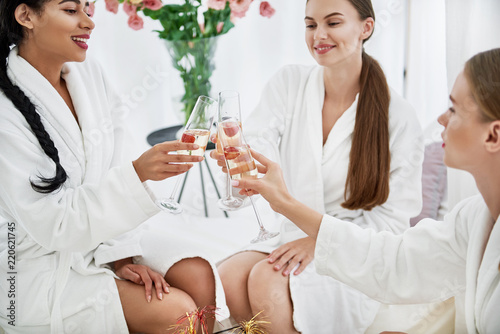 Happy event. Lovely young ladies in white bathrobes holding glasses of champagne and toasting. Vase with flowers on blurred background