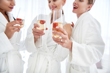 Celebration At Spa. Smiling Girls Holding Alcohol Drinks With Strawberry. Women Wearing Soft Bathrobes And Toasting