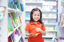 Asian Children Or Kid Girl Red Shirt Happy Smile And Shopping Or Choose Tale Or Story Book And Read On Bookshelf In Bookstore Or Library Room At Kindergarten School Or Nursery For Learn And Study