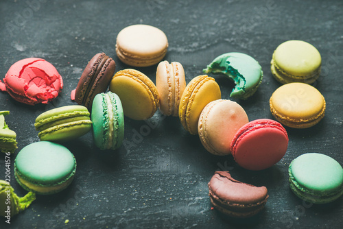 Sweet colorful French macaroon cookies dessert variety over black background, selective focus, horizontal composition
