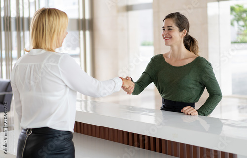 Foto Office receptionist greeting corporate partner with handshake