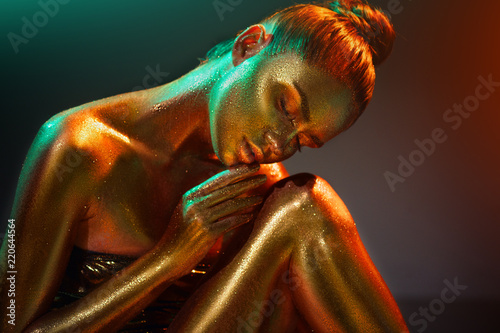 Fashion Model Girl In Colorful Bright Golden Sparkles On Her Body In Neon Lights Posing Portrait Of Beautiful Girl With Glowing Makeup Glitter Vivid Neon Skin Body Art Buy This Stock