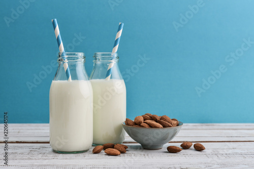 Almond milk in bottles with almonds