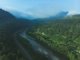 aerial view for mountains with forest. mist comes up from woods