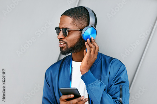 Poster Magasin de musique Listen Music. Man With Headphones And Phone In Fashion Clothes