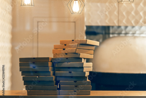 A pile of pizza boxes in a pizzeria.