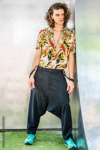 Hispanic American Artist with brown curly hair in New York, wearing colorful patterned short sleeve shirt, baggy loose pants with suspenders, patterned sneakers, hanging old key as necklace Wallpaper Mural