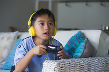 Young Latin Little Child Excited And Happy Playing Video Game Online With Headphones Holding Controller Having Fun Sitting On Couch In Kid Gaming Addiction