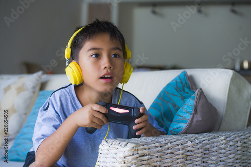 young Latin little child excited and happy playing video game online with headph Wallpaper Mural