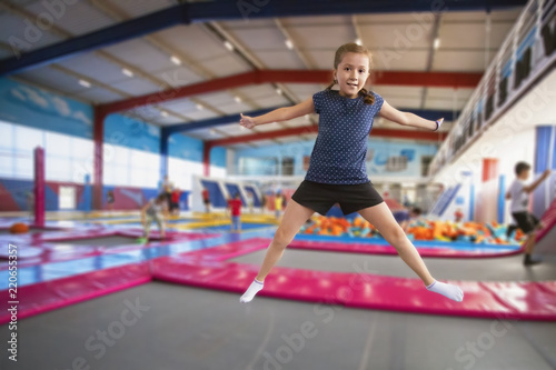 Poster Attraction parc joyful little girl with pigtails and a smile on her face jumping on the trampoline