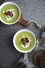 Overhead Image Of Creamy Green Pea Soup With Fried Bacon And Herbs On Gray Background