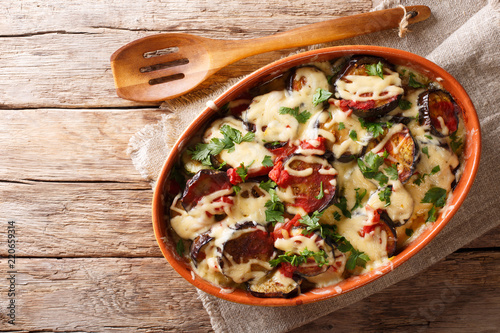 Vegetable casserole from eggplants with tomatoes and mozzarella cheese and parmesan close-up in a dish for baking. horizontal top view from above