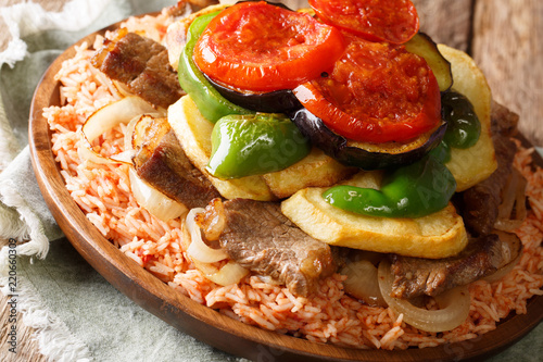 Middle Eastern Dish Maklouba or Makloubeh rice with meat and vegetables close-up on a plate. Horizontal
