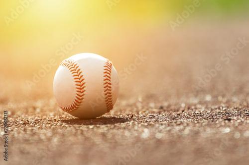 Fotografiet  Baseball ball on pitchers mound. Baseball field at sunset