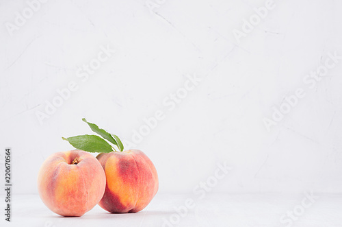 Fresh ripe peaches with green leaf on white wood board, copy space.