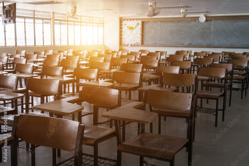 Fototapeta Empty classroom with vintage tone wooden chairs. Back to school concept.