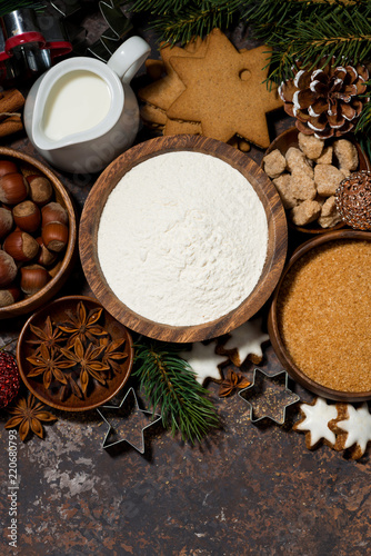 ingredients for Christmas baking on dark background, vertical top view