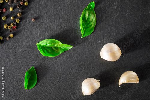 Photo Garlick fennel pepper of basilic on a black stone background