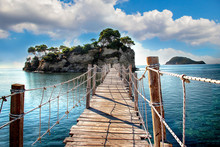 The Wooden Bridge Overlooking The Sea Leads To An Island With Palm Trees. It's A Rope Bridge. It Is Located In Zakynthos, Greece.