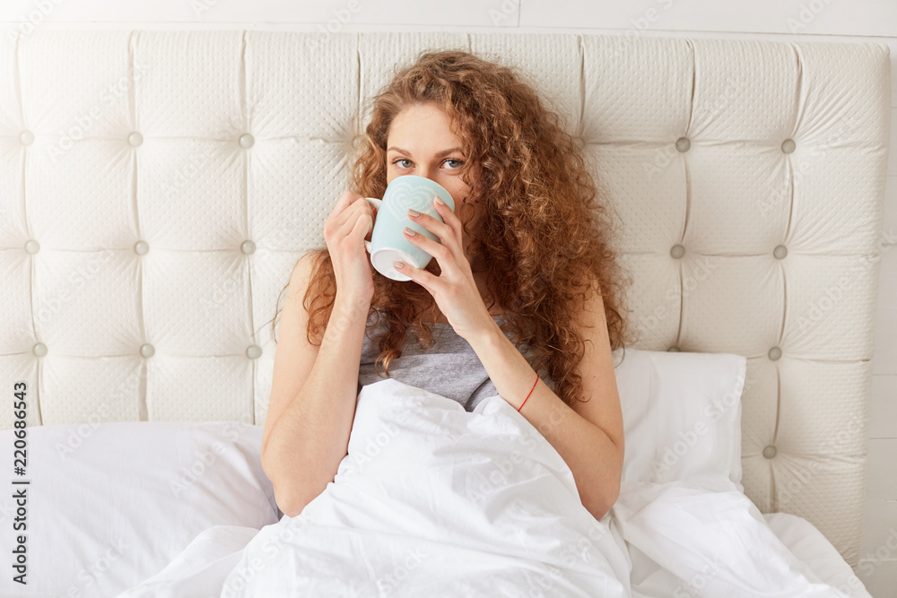 Fototapeta Horizontal shot of pleasant looking delighted European woman drink fresh coffee in bed, has curly bushy hair, dressed in pyjamas, enjoys domestic atmosphere. People, rest and bedding concept