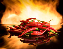Hot Chilli With Burning Fire On Black Surface