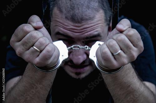 Fotografia, Obraz  Portrait of handcuffed criminal man imprisoned.