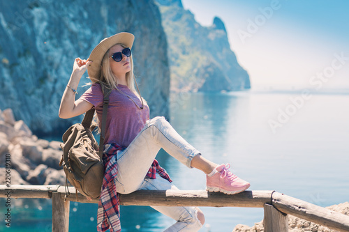 Young woman backpacker traveler in fashion clothes in a country style in  the mountains. Girl hiking in sneakers 9ccd5345d6dd