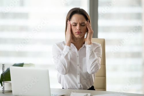 Obraz na plátne  Stressed frustrated female employee feeling strong headache at workplace massagi