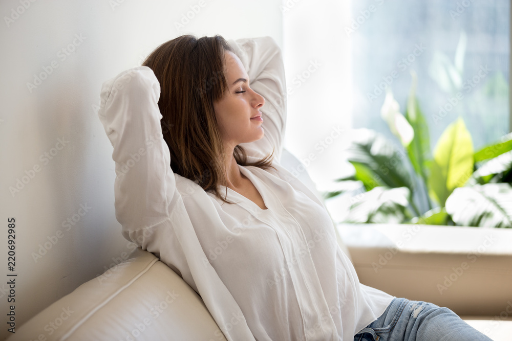 Fototapeta Relaxed calm woman resting breathing fresh air feeling mental balance enjoying wellbeing at home on sofa, satisfied young lady taking pleasure of stress free weekend morning stretching on couch