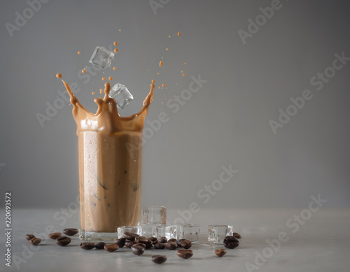 Iced coffee splash with ice cubes and beans against grey concrete