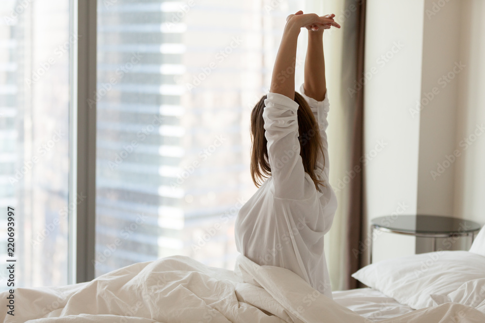 Fototapeta Woman waking up happy stretching sitting on comfortable bed looking out of big skyscraper window in modern hotel bedroom enjoying good morning and city view starting new day, wellbeing concept