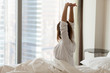 canvas print picture - Woman waking up happy stretching sitting on comfortable bed looking out of big skyscraper window in modern hotel bedroom enjoying good morning and city view starting new day, wellbeing concept